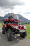 A man on quad before the mountains in Bavaria Stock Photos