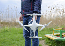 A man with a quadrocopter in his hands. A white drone is being prepared for the flight. Phantom. A man with a quadrocopter in his hands. A white drone is being Stock Photos