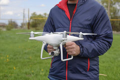 A man with a quadrocopter in his hands. A white drone is being prepared for the flight. Phantom. A man with a quadrocopter in his hands. A white drone is being Stock Photo