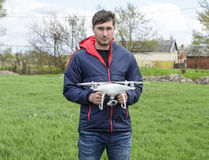 A man with a quadrocopter in his hands. A white drone is being prepared for the flight. Phantom. A man with a quadrocopter in his hands. A white drone is being Royalty Free Stock Photos