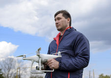 A man with a quadrocopter in his hands. A white drone is being prepared for the flight. Phantom. A man with a quadrocopter in his hands. A white drone is being Royalty Free Stock Image