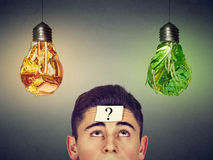Man with question looking at junk food vegetables light bulbs