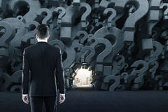 Man in a question mark room, close up. Rear view of a businessman in a black suit standing in an empty room with gray 3d question marks on the walls. There is a Stock Photo