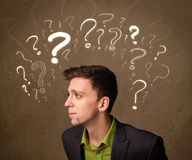 Man with question mark symbols around his head Royalty Free Stock Image