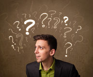 Man with question mark symbols around his head Stock Image