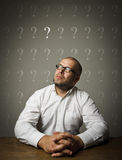 Man and question marks. Man in white and question marks above head Stock Photos
