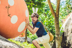 Man with rabbit ears having fun with traditional Easter eggs hunt, outdoors. Celebrating Easter holiday. royalty free stock image
