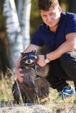 Man with raccoon Stock Images