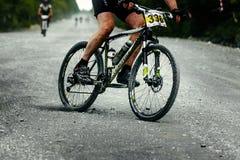 Man racerbilcyklistmountainbiker som är sluttande på grusvägen Royaltyfri Bild