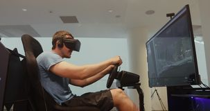 Man racing in VR headset. Side view of gamer sitting and playing racing simulator game in virtual reality headset stock video