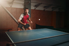 Man with racket in action, playing table tennis Stock Photo