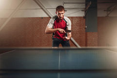 Man with racket in action, playing table tennis Stock Photos