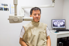 Man with radiation protection vest receiving dental  X-Ray at a dentist Royalty Free Stock Image