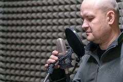 Man radio DJ speaks into the microphone in the workplace closeup royalty free stock photo