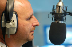 Man with radio microphone. Male radio presenter of local radio station presenting a show live Royalty Free Stock Photography