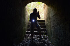 Man with radio set and flashlight enters tunnel Stock Photo