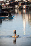 Man on raft - squatter shanty area. Man paddling down river on makeshift raft. Heavily polluted Paranaque River, Manila, Philippines. Squatter / Shanty housing Stock Photos