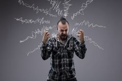 Man in a rage throwing a temper tantrum. Screaming and clenching his fists with hand drawn squiggles of emotion or sound emanating from his head on a chalkboard Royalty Free Stock Image