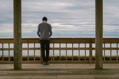 Man on railing overlooking ocean