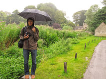 Man in the rain with umbrella. A young man with camera and umbrella standing in the rain and waiting Royalty Free Stock Images