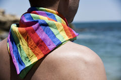 Man with a rainbow flag in front of the ocean Royalty Free Stock Image