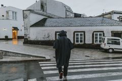 Senior man with a rain coat in a village. stock photography