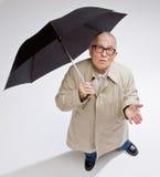 Man in raincoat holding umbrella checking for rain. Curious man in raincoat holding umbrella checking for rain Stock Photo