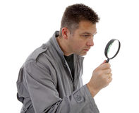 Man with raincoat is looking with magnifying glass over white ba Royalty Free Stock Images