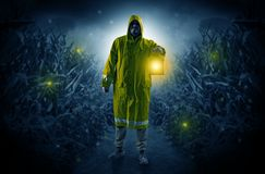 Man coming out from a thicket with lantern. Man in raincoat at night coming from thicket and looking something with glowing lantern Royalty Free Stock Photography