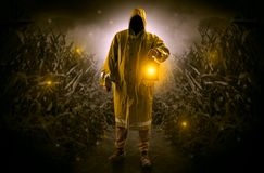 Man coming out from a thicket with lantern. Man in raincoat at night coming from thicket and looking something with glowing lanternn Stock Image