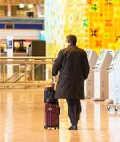 TOKYO, JAPAN - NOVEMBER 7, 2017: Man in a raincoat with a suitcase at the airport. Back view. With selective focus royalty free stock images