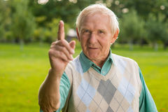 Man with raised finger. Old male looking at camera. Remember what I've taught you. Important lesson in life Stock Photo
