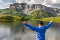 Man with raised hands standing on the shore of a mountain lake and enjoy the view Stock Image