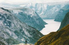 Man raised hands traveling at Naeroyfjord mountains. Landscape aerial view Lifestyle concept adventure active vacations outdoor trekking in Norway Royalty Free Stock Photo