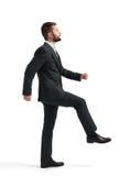 Man raised one leg like climbing stairs Royalty Free Stock Photography