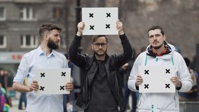 The man raised a poster at the rally. Boys protesting in protest. Three persons. People at the demonstration with banners in their hands look into camera and