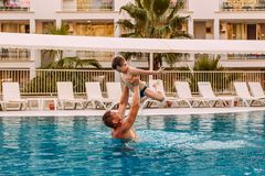 A man raises a child in the pool. happy father and son on vacation stock image