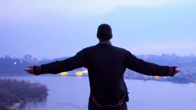 Man raises hands to sky, feels strength and self-confidence to conquer world