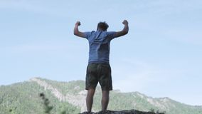 Man raises hands up standing back on mountain top morning sun shine slow motion. stock video footage