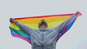 Man raises rainbow flag, march for LGBT right, solidarity with same-sex marriage. Stock footage stock video