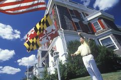 Man Raising American and Maryland Flags Royalty Free Stock Image