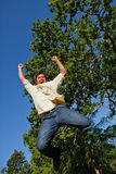 Man raising both of his arms and both of his legs as he jumps in Royalty Free Stock Photo