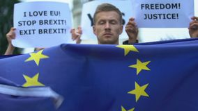 Man raising flag of European Union, protesting Brexit, no borders for migration. Stock footage stock video