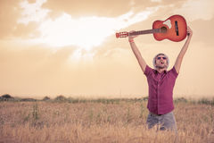 Man raising guitar up in the air in wheat field Royalty Free Stock Photo