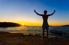 Man raising hands at sunset on the beach Stock Photo