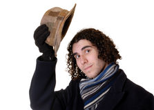 Man raising hat. Young man with curly hair in hat, coat and scarf, wrapped up for the cold raising hat in polite greeting - isolated on white Stock Images