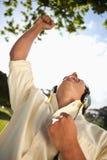 Man raising his arm while using headphones Stock Photos