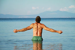 Man Raising His Hands or Open arms standing back looking to sea blue sky horizon. Stock Image