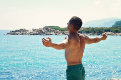 Man Raising His Hands or Open arms standing back looking to sea blue sky horizon. Royalty Free Stock Images