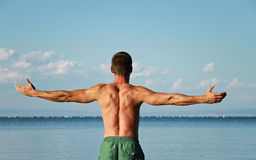Man Raising His Hands or Open arms standing back looking to sea blue sky horizont. Royalty Free Stock Photos